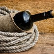 Bottle wrapped with rope — Stock Photo