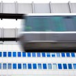 Sky-Train passing fast in front of office building — Stock Photo