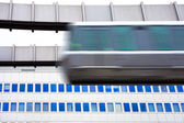 Sky-Train passing fast in front of office building — Stok fotoğraf