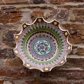Ceramic bowl on stone wall — Stock Photo