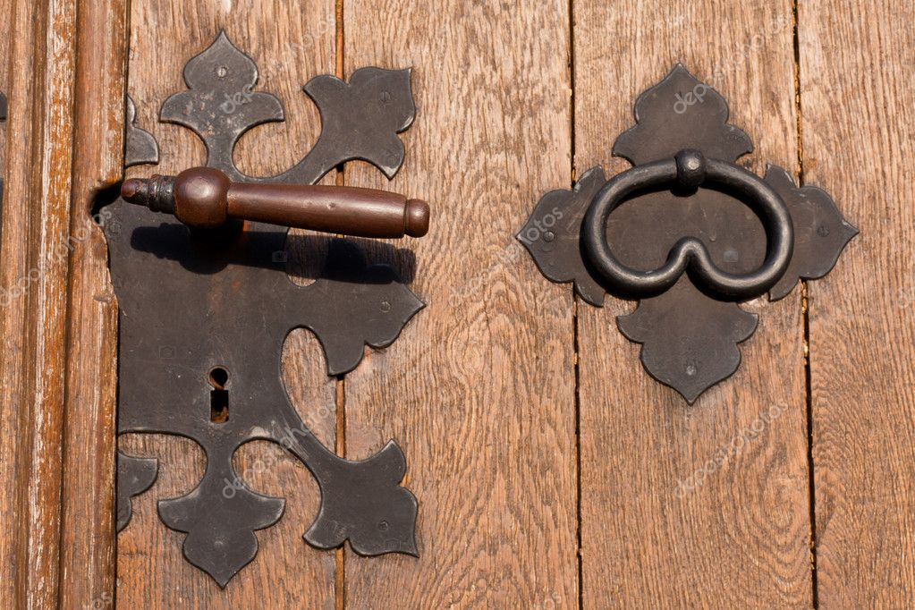 Iron door handle knob and keyhole on heavy wooden door.  Stock Photo #6057080