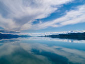 Dramatic sky reflected on calm lake — Stock Photo