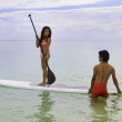 Beachboy teaches young woman to paddleboard — Stock Photo