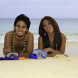 Asian couple lounging on the sand of a hawaii beach — Stock Photo #5462397