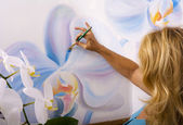 Female artist painting phalaenopsis orchids — ストック写真