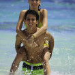 Couple in the ocean riding piggyback — Stock Photo #6052404