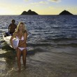 Stock Photo: Couple in their forties with their outrigger canoe