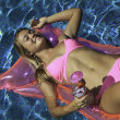 Girl in pink bikini floating in a pool - Stock Photo