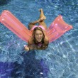 Girl in pink bikini playing in a pool — 图库照片