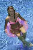 Girl in pink bikini playing in a pool — Stok fotoğraf