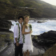 Newlywed couple on lava cliffs by the pacific ocean — Stock Photo