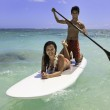 Young couple with their paddle board in hawaii — Stock Photo
