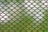 Rusty fence on blue sky — Stock Photo