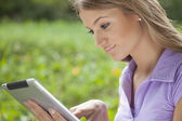 Woman using tablet computer in park — Stock Photo