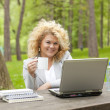 Woman using laptop in park — Stock Photo