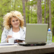 Woman using laptop in park on wooden table — Stock Photo #6280716