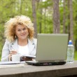 Woman using laptop in park on wooden table — Stock Photo