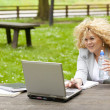 Woman using laptop in park and drink water — Stock Photo