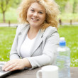 Stock Photo: Woman using laptop in park