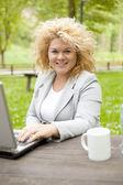 Bella donna bionda usando il portatile nel parco — Foto Stock