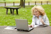 Mujer utilizando laptop en parque y beba agua — Foto de Stock
