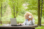Woman using laptop in park and drinking — Stock Photo