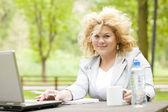 Kvinna med laptop i park — Stockfoto