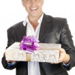 The happy smiling man on a white background with a celebratory gift — Stock Photo #6648172
