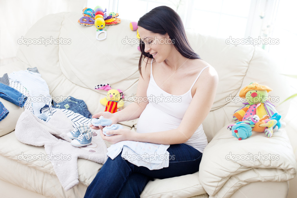 Happy pregnant caucasian brunette  woman waiting arround toys for baby   Stock Photo #5412936