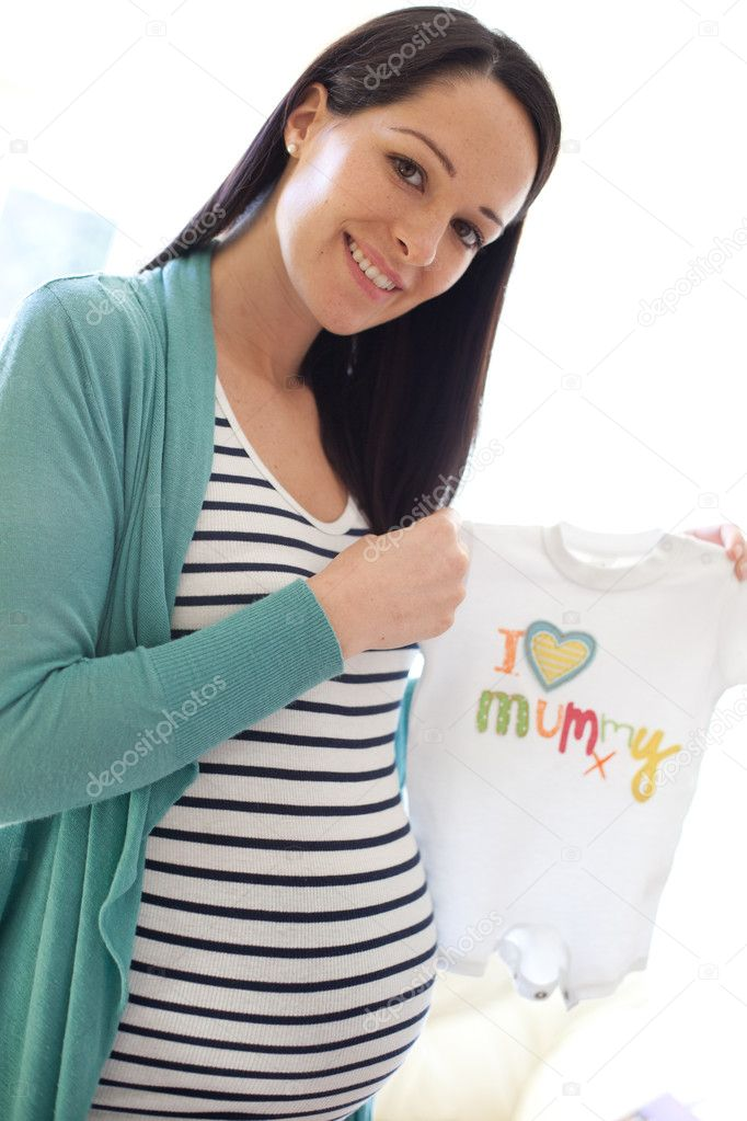 Portrait of a happy young pregnant woman holding i love mummy shirt for her unborn child. — Stock Photo #5413012
