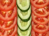 Segmenten van tomaat en komkommer als achtergrond. — Stockfoto