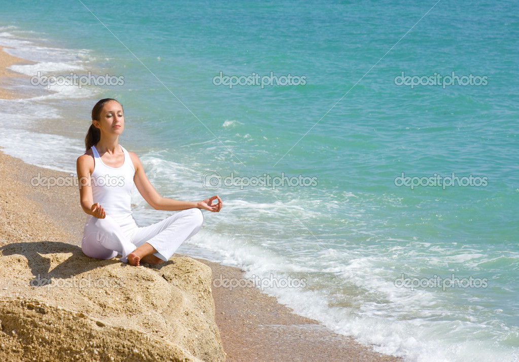 Young attractive brunette sitting in lotus position on the beach — Stock Photo #6152964