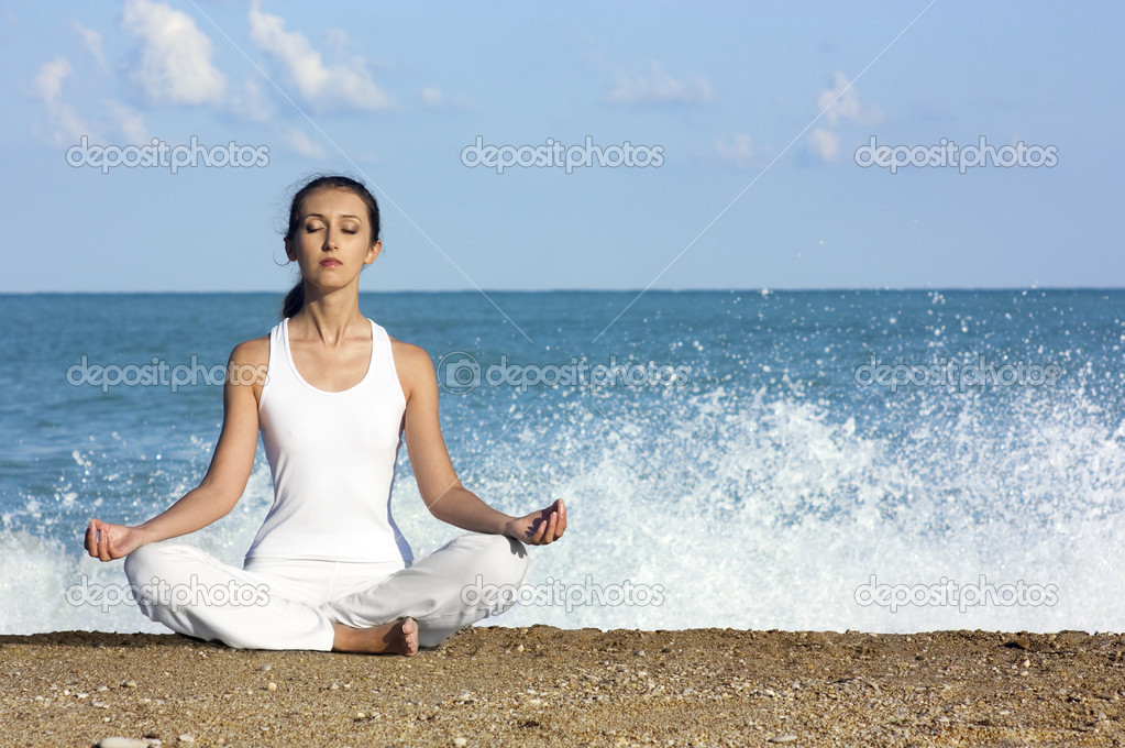 Young attractive brunette sitting in lotus position on the beach — Stock Photo #6245465