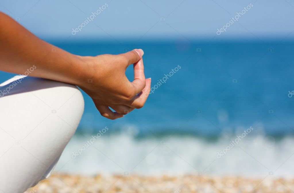 Woman practicing yoga near the ocean. Beautiful meditation details. — Stock Photo #6549542