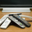 Stock Photo: Many tv controllers near televisor