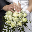 Groom and bride showing gold rings and flowers — Stock Photo