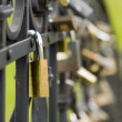Many metal locks are hanging on black fence - Stock Photo