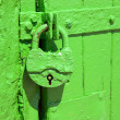 Green metal lock is hanging to protect entrance through doors - Stock Photo