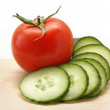 Cucumber and tomato on a wooden board — Stock Photo