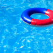 A colorful inflatable ring floating in a swimming pool — Stock Photo #6670917