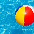 Colorful beach ball floating in swimming pool — Stock Photo #6670922