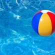 Colorful beach ball floating in swimming pool — Stock Photo #6670937