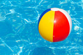A colorful beach ball floating in a swimming pool — Zdjęcie stockowe