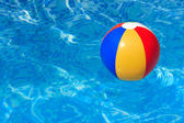 A colorful beach ball floating in a swimming pool — Stok fotoğraf