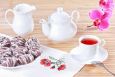 Cup of tea, teapot and chocolate iced spice cakes — Stock Photo