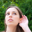 Stock Photo: Relying on hand-ear listening young woman
