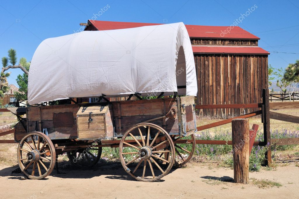 An old vintage covered wagon is shown in front of a barn in the desert town of Pioneertown, California. — Stock Photo #5651839