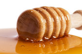 Closeup of a honey dipper in a puddle of honey — ストック写真