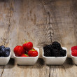 Row of wild berries in bowls - Stock Photo