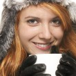 Stock Photo: Smiling young redhead womin winter dress holding coffee cup